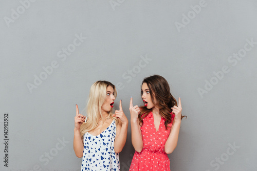 Photo  Shocked young women looking aside and pointing.