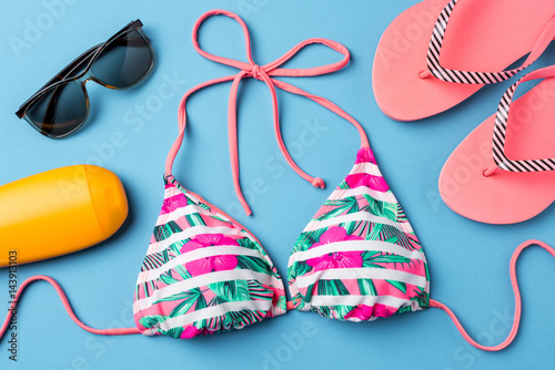 Fotomural Colorful swimsuit with beach accessories on blue background
