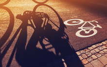 Shadow Of Unrecognizable Cyclist On Bicycle Lane