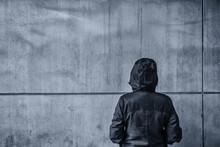 Unrecognizable Hooded Female Person Facing Concrete Wall