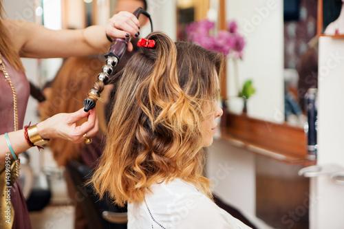 Hairdresser using curling tongs on customer's long brown hair in salon