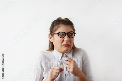 Photo Headshot of disgusted Caucasian student girl in shirt and glasses looking aside with fearfyl and suspicions, holding her fist up