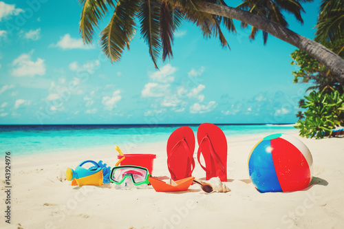 Photo  Colored slippers, toys and diving mask at beach