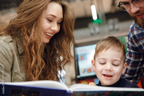 Aluminium Prints Amusement Park Cropped image of Young family reading book in supermarket
