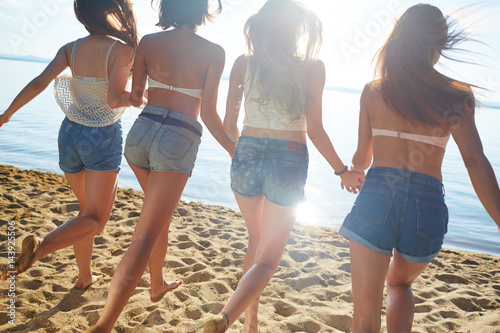 Photo  Group of carefree girls running on sand