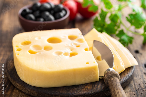 Foto  Delicious Swiss yellow cheese on dark wooden rustic background closeup