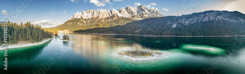 Poster de jardin Reflexion Landscape scenery with a island in the foreground on an alpine lake and the Zugspitze in the background