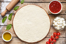 Raw Dough Preparation Or Pizza With Ingredient: Tomato Sauce, Mozzarella, Tomatoes, Basil, Olive Oil, Spices Served On Rustic Wooden Table. Flat Lay Style, Copy Space For Text. Margherita