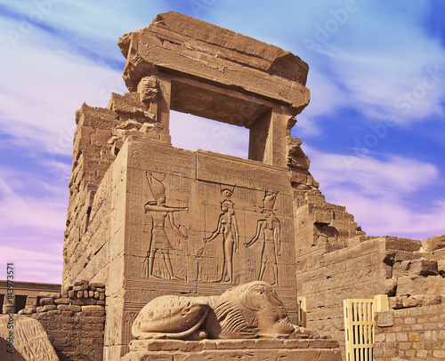 Foto op Canvas Remains of an Egyptian temple with a statue in the foreground and a blue sky with clouds in the background. Dendera, Egypt.
