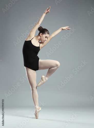 Young beautiful ballerina dancing on light background Canvas Print