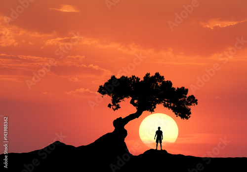 Deurstickers Baksteen Man under the crooked tree on the background of sun. Silhouette of a standing sporty man on the mountain and colorful orange sky with clouds at sunset. Beautiful landscape in the evening. Travel