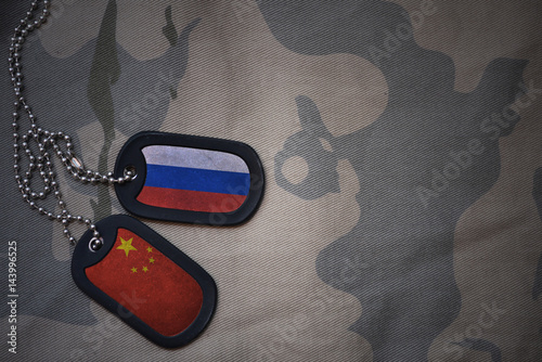 Fotografia  army blank, dog tag with flag of russia and china on the khaki texture background