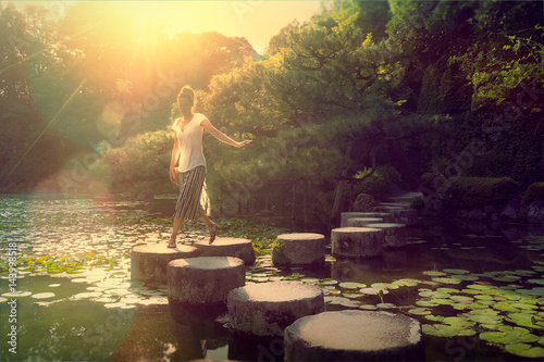 Poster Zen Young woman stepping on lake stone path in Kyoto Japan at sunset