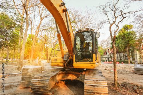 Plakat Koparka lub koparko-ładowarki na budowie, tło zachód, utwór typu ładowarki koparka maszyna robi robót ziemnych praca na budowie