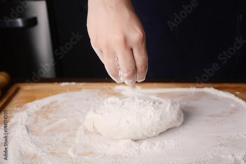 Deurstickers Bakkerij Woman hand adding flour to dough.