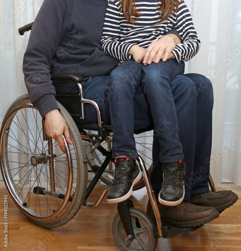 Fotografia  disabled parent in a wheelchair with his little daughter