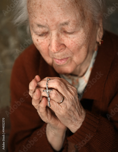 Fotografie, Obraz  Old woman praying and  holding silver rosary