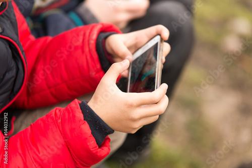 Zdjęcie XXL Chłopiec bawić się gry komputerowe na telefonie komórkowym