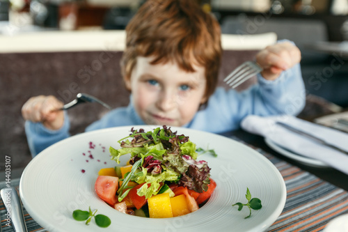 Red haired boy with forks eating salad