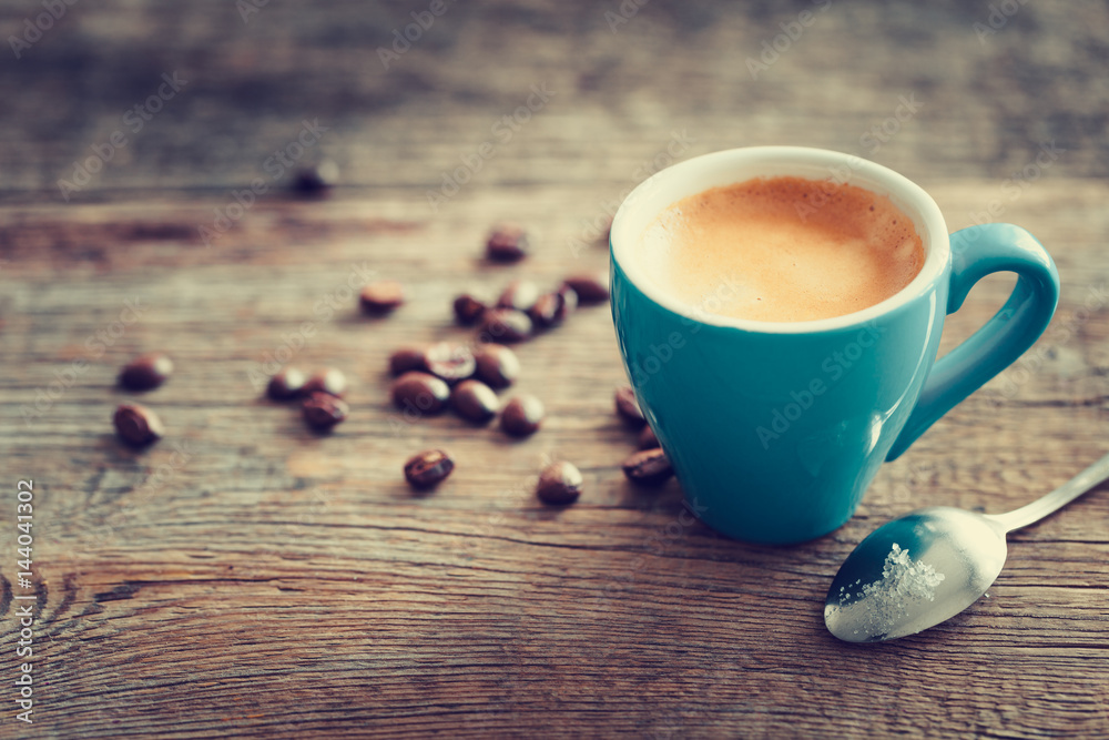 Espresso coffee cup with beans on wooden board. Retro stylized.