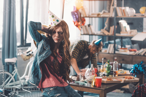 Fotografia, Obraz confused woman in birthday hat, man cleaning behind in messy room after party