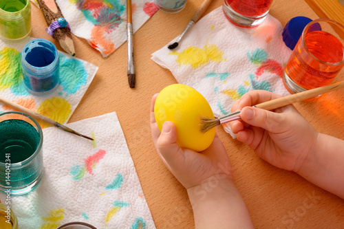 Photo  Little girl painting easter eggs with paintbrush