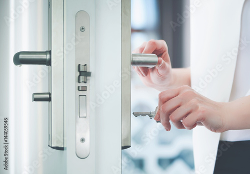 Locking or unlocking door with key in hand Canvas Print