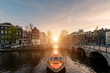 canvas print picture - Amsterdam canal cruise ship with Netherlands traditional house in Amsterdam, Netherlands.