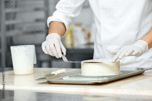 Photographie Young professional chef glazing a delicious cake