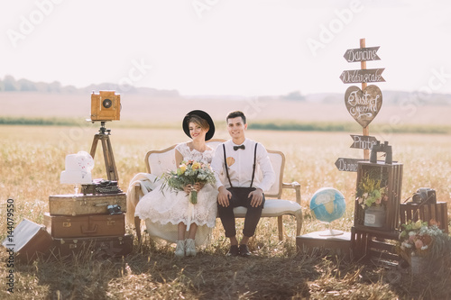 Photo  The smiling bride with bouquet and happy groom in vintage suit are sitting on the old-fashioned sofa surrounded by flowers, wooden plaques with signs, suitcases at the background of the spring field