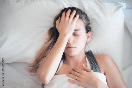 Cuadros en Lienzo Donna con mal di testa a letto, emicrania e sinusite