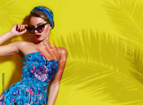 Photo  A beautiful young tanned girl with a headscarf on her head and wearing sunglasses stands near a yellow wall in the south