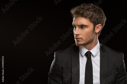 Serious handsome businessman in a suit on black background