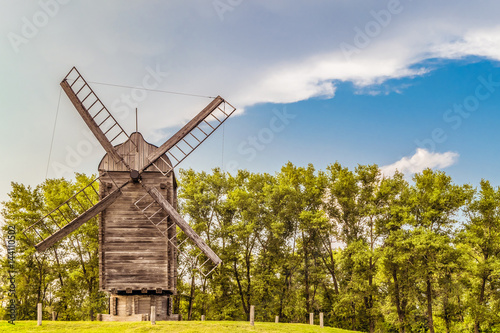 Poster Molens Large Russian wooden windmill on a background of green trees. Summer landscape.