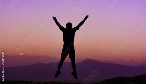 Silhouette of a happy man enjoying his trip in Nepal with blurred himalayan range on background