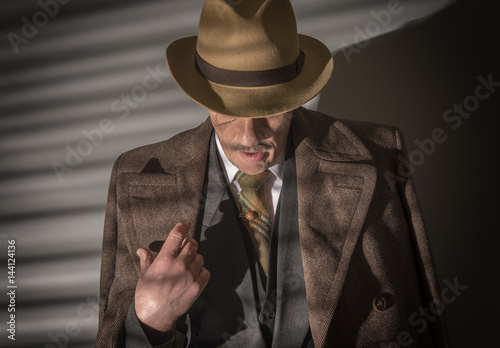 Mature man dressed as a 1940s gangster, on a grey background Canvas Print
