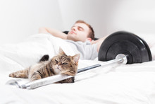 A Male Bodybuilder Is Sleep After Training With A Cat And A Barbell On A White