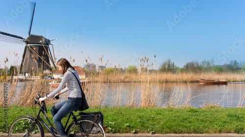 Woman bikes along windmill Wallpaper Mural