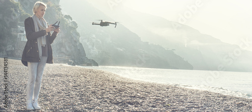 Fotografie, Obraz  Young girl flying drone over italian coast.