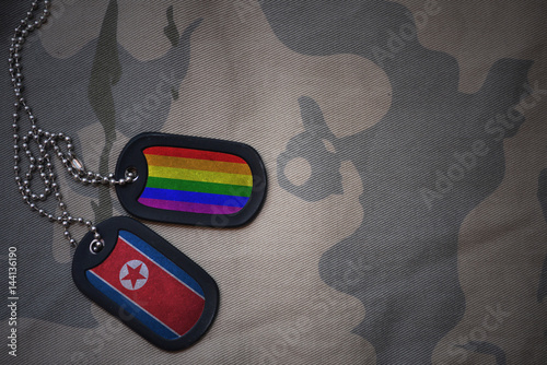 Stampe  army blank, dog tag with flag of north korea and gay rainbow flag on the khaki texture background
