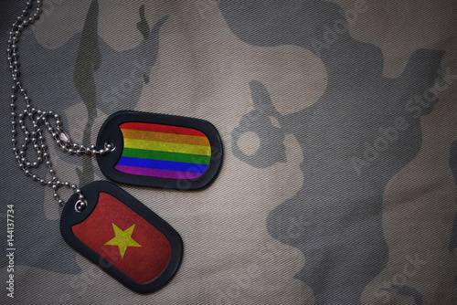 Stampa su Tela  army blank, dog tag with flag of vietnam and gay rainbow flag on the khaki texture background