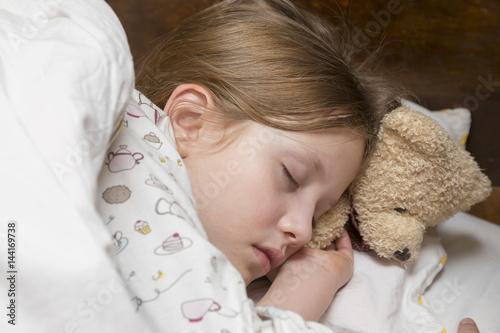 Fototapeta dziewczynka śpiąca w nocy z udzikiem obraz