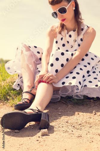 Fotografie, Tablou Pinup Girl mit Petticoat und Sonnenbrille sitzt am Wegrand