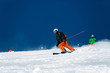 A skier during descent at a ski resort. Beautiful winter landscape with snow-topped mountains.