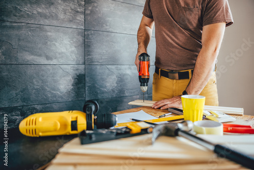 Man drilling wood with battery power Drill