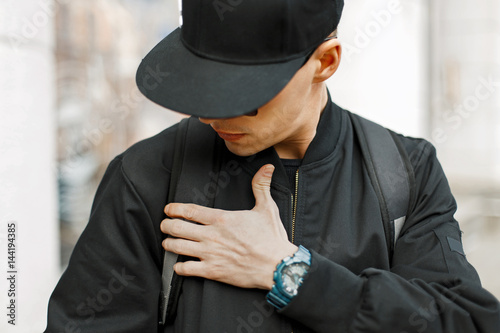Valokuva  Fashionable man in a black baseball cap and black jacket in the city