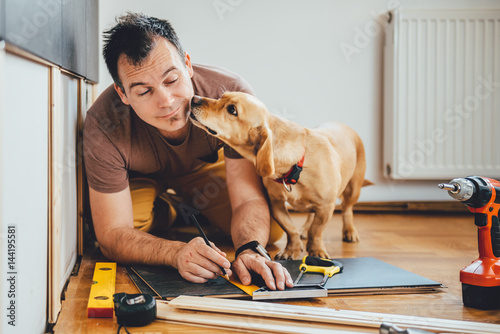 Photo  Man and his dog doing renovation work at home
