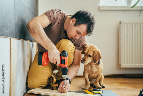 Foto Man and his dog doing renovation work at home