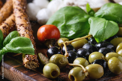 Recess Fitting Appetizer Mediterranean appetizer antipasti board with green black olives, feta cheese, mozzarella, capers, pepper, basil with grissini bread sticks over black wood burnt background. Close up