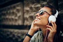 Happy Young Woman Listening To...